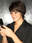 Hispanic woman (20-30) smiles while texting with a mobile phone.
