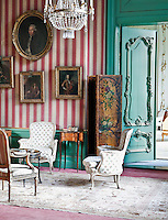 A collection of 18th century portraits hangs on the striped walls of an ante-room