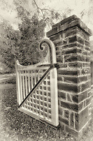 A black and white view of an downtown Oakville park garden gate.