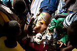 The body of an education minister is prepared for burial on May 18, 2010, after he and his colleagues were ambushed by the LRA and brutally murdered.