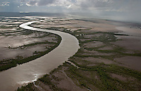 River of muddy water flows through the tidal mudflats just outside town of Wyndham.  The aerial scene shows rains wash the dirt into the rivers and creeks and the silt runs out to the Cambridge Gulf in Kimberley.