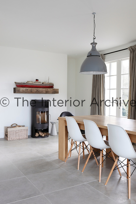 A rustic beam used as a mantelpiece above a wood-burning stove in the dining area displays a model liner