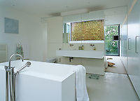 A free-standing bath in a contemporary en-suite bathroom with a view through to the bedroom