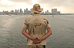 """With the San Diego skyline receding into the distance, a marine stands at attention - part of a ceremony known as """"manning the rails"""" - as the amphibious assault ship USS Belleau-Wood aboard which he stands slips out of San Diego harbor on its way towards Iraq.  The marine is one of the 2,220 members of the 11th Marine Expedition Unit which will arrive in Iraq in mid-July for a scheduled seven-month-deployment to replace elements of the 1st Armored Division which has been in Iraq for nearly a year-and-a-half."""