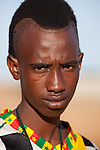 A young Fulani musician from a village in northern Burkina Faso sports an in mode hair style.