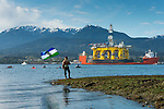 A small group of environmental protesters were on hand to greet the 400 foot tall Polar Pioneer, an oil drilling platform brought in from Asia piggybacked on a large ship, on its way to Seattle and maybe Alaska. The protesters' boats and kayaks were ordered to keep 100 yards away from the platform, and that was enforced by the Coast Guard. Earlier, Greenpeace activists boarded the vessel at sea near Hawaii and occupied it for several days but were ordered off by a federal judge. The flag is the Cascadia flag. http://www.cascadianow.org/