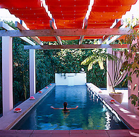 Designer Antonia Hutt relaxes in her outdoor swimming pool, which is covered with a retractable orange awning