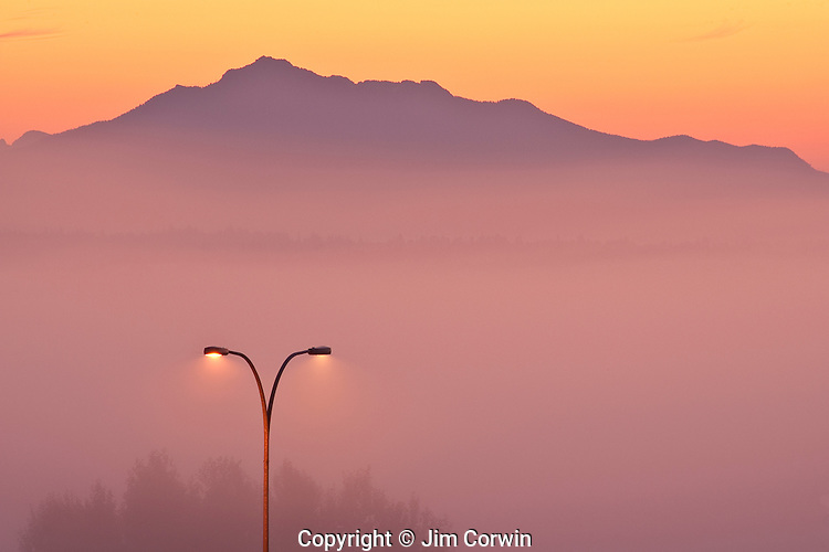 Cascade Mountain Range sunrise with fog in Snohomish Valley with light post