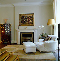 A large armchair and footstool stand in the corner of this understated living room which is decorated in white with shades of gold