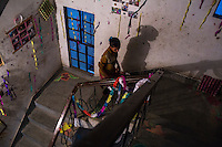 A daughter of a woman in prostitution walks up the stairs in the Guria Non-Formal Education center in the middle of the Shivdaspur red light district, Varanasi, Uttar Pradesh, India on 20 November 2013. These girls, daughters of women in prostitution, strive to break stigma and the cycle of prostitution by learning skills that will allow them to work in regular jobs.