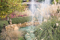 A small gnome perches on the stonework beneath an ornamental tree as fountains geyser up to mimic the frothy plumes of a giant Maiden Grass, Miscanthus sinensus, at the Chandor gardens in Weatherford, Texas