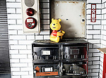 An inflatable Pooh Bear toy sits atop the letter boxes of an aging apartment building in Tokyo, Japan.