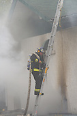fireman wearing a new black bunker climbing up a ladder with a water hose