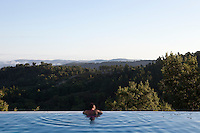 A woman relaxing in an infinity pool enjoying the panoramic view of the surrounding countryside