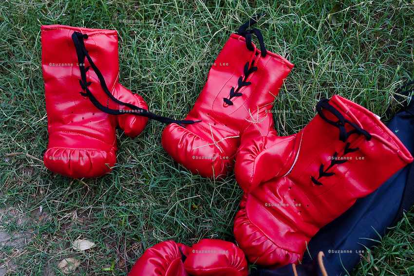Boxing gloves lay on the grass as Razia Shabnam (unseen) conducts a boxing training session with a group of girls from an NGO in a park in Basduni, Tolly Gunge, Calcutta, West Bengal, India. Razia Shabnam, 28, was one of the first women boxers in Kolkata. She was also the first woman in her community to go to college. She is now a coach and one of only three international female boxing referees in India.  Photo by Suzanne Lee for Panos London
