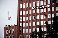 Oslo, Norway, 23.07.2011. Stoltenbergs labour party headquarters, with shattered windows and the Norwegian flag of half mast. Oslo awakes to shocking messages of the total bodycount after yesterdays massacre. A total of 91 persons were killed in the massacre in Utøya right outside Oslo. Seven of those died when a car bomb was detonated outside the main government biuilding in the heart of Oslo, friday 22. of July. Foto: Christopher Olssøn.