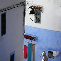 Street corner with lamp in the medina or old town of Chefchaouen in the Rif mountains of North West Morocco. Chefchaouen was founded in 1471 by Moulay Ali Ben Moussa Ben Rashid El Alami to house the muslims expelled from Andalusia. It is famous for its blue painted houses, originated by the Jewish community, and is listed by UNESCO under the Intangible Cultural Heritage of Humanity. Picture by Manuel Cohen