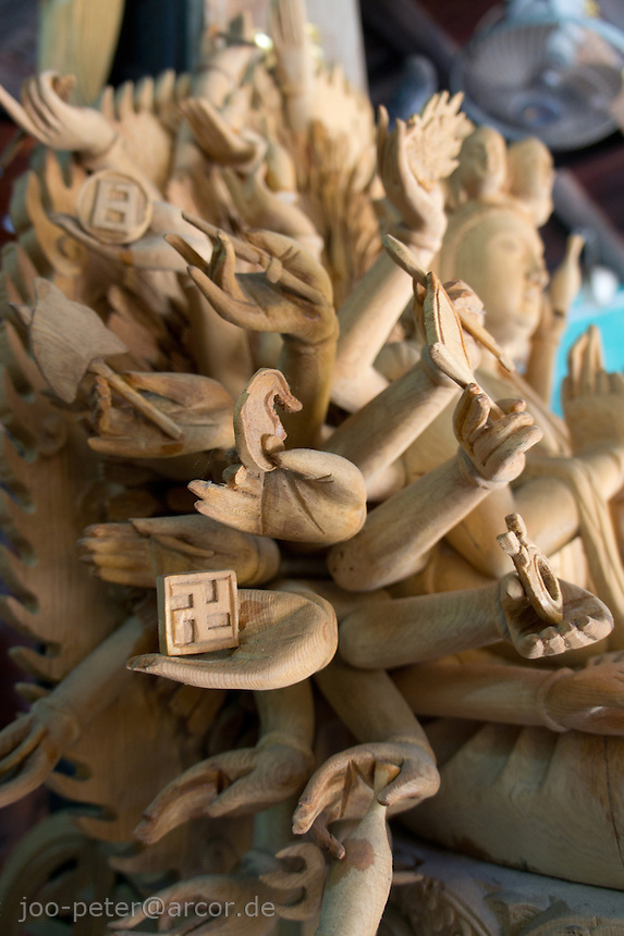 """wood sculpture """"Buddha with thousand arms"""" in workshop,  city Hoi An, Vietnam. """"Buddha with thousand arms""""   is a popular name for Phat Mau Chuan De Bodhisattva (actually showing 18 arms, each with a specific meaning). . Vietnamese belief is a blend of Buddhism, Taoism and animism."""