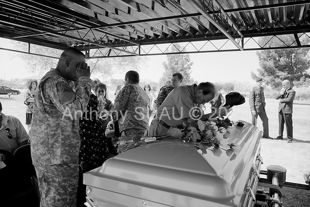 Tucson, Arizona.USA.March 16, 2007..At the Evergreen cemetery family and  friend pay their respects just after the funeral services for Staff Sgt. Darrel D. Kasson, 43, of Florence, Ariz. He died March 4 in Tikrit, Iraq, of wounds suffered when an improvised explosive device detonated near his vehicle at Bayji, Iraq. He was assigned to the 259th Security Forces Company, Phoenix.