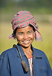 A woman pauses from harvesting rice in the Cambodian village of O Kroich, where residents are members of the Kouy indigenous group. This woman participates in a rice bank sponsored by the Community Health and Agricultural Development program of the Methodist Mission in Cambodia.
