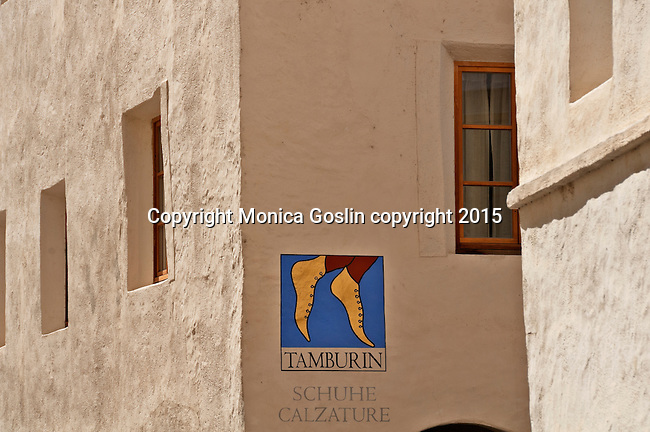 Store sign for a shoe store painted on the wall in the Medieval walled town that is the smallest town in the Southern Alps with just over 800 people