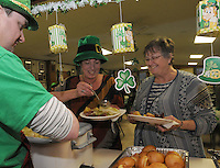 NWA Democrat-Gazette/FLIP PUTTHOFF <br /> ST. PATS AT ST. ANDREWS<br />  James Crews (left) staffs the serving line while Twila Strickert (center) and her mom, Jeanette Strickert, dish up corned beef and cabbage during the annual St. Patrick's Day dinner Saturday March 12, 2016 at St. Andrew's Episcopal Church in Rogers. The church men's group cooks the main course and women of the church bring desserts. The St. Patrick's Day meal has been a tradition at the church for years, the cooks said.