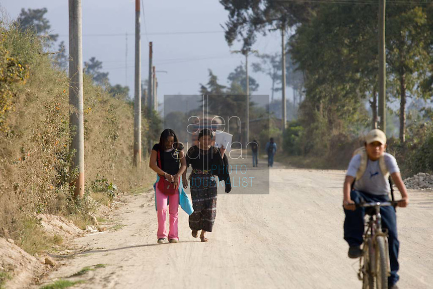 Maria (right), 16, and her friend, Alma de Los Angeles Sambrano Montufa, 15, walk away from Legumex, a vegetable and fruit company that exports to the United States, in Chimaltenango, Guatemala on Thursday, March 8, 2007, a payday. Alma recently quit the company after a year and a half. Maria still works there, but injured her wrist on the job and couldn't work today.