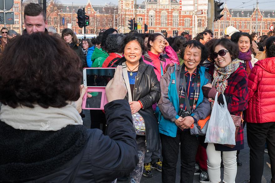 Nederland, Amsterdam, 19 maart 2015<br /> Groep chinezen verzameld zich buiten voordat ze de stad in gaan. De aanwezigen worden gecheckt. Nog even een groepsfoto maken met de smartphone, daarna begint een toertje door de stad.<br />  <br /> Foto: Michiel Wijnbergh