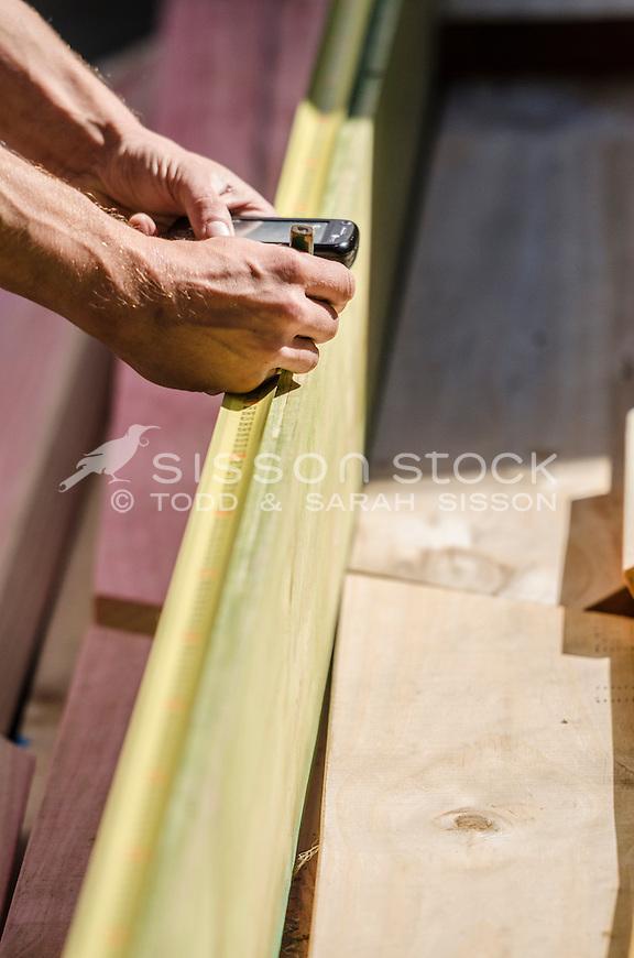 New Zealand Photos | Builder measuring wood, NZ | Sisson Stock Photos