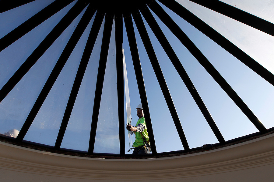 Construction worker Traon Jordon with Semco Services, Inc. on Tuesday removed the skylight glass from the University of Virginia's Rotunda dome as part of roof replacement of the iconic building. Following removal of the glass, crews will install a temporary black membrane on the roof to protect the building's interior between the time the old skylight is removed and a new one is installed, around mid-March. While the Rotunda will remain open during the work, the Dome Room will have only limited access to visitors for about 12 weeks.<br /> The work is part of the first phase of the Rotunda renovations, which involves replacing the leaking roof and the oculus, as well as repairing the exterior brick walls, windows and ornamental sheet metal. Future phases include replacing the elevator, restoring the portico column capitals and improving the mechanical, electrical, plumbing, sprinkler and data systems.<br /> The total project, expected to take several years, will cost around $50 million. It is being funded through a mixture of state appropriations and private gifts. Photo/Andrew Shurtleff