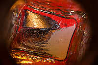 """Beauty at the Bottom: Tequila Sunrise 1"" - This image is a photograph of a tequila bottle looking right down the mouth of the bottle."