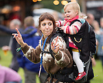 Electric Fields music festival, crowd women dancing with small child on back at Drumlanrig Castle near Dumfries Scotland