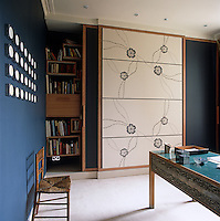 In this home office a Japanese-style sliding screen conceals the book shelves
