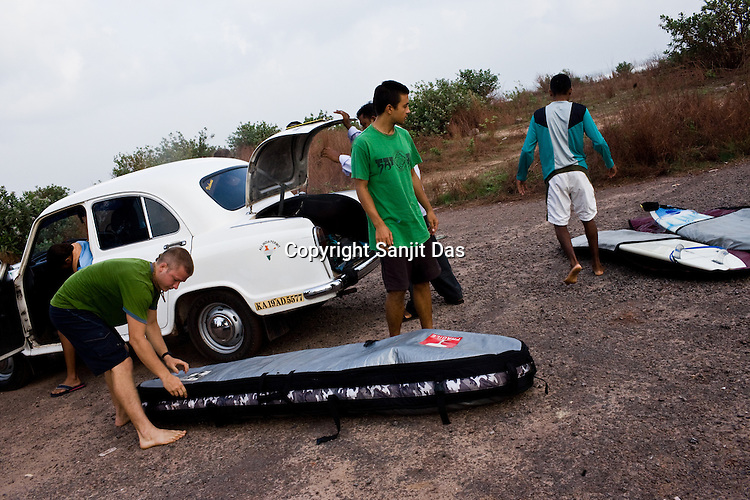 "Devotees unpack the surfing boards and get ready for the ride to the beach for a surfing session on the Arabian Sea in Mangalore beach, Karnataka, India.  ..Krishna devotees in the Gaudiya Vaishnava tradition of Hinduism, they are known collectively as the ""surfing swamis."" The ""surfing ashram"" is growing in popularity and surfing here is a form of meditation, a spiritual practice leading to heightened states of awareness."