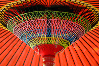 Detail of a red Japanese wagasa parasol, tied with brightly coloured threads in the traditional manner.