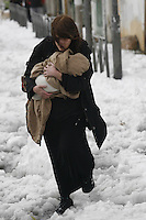 Israeli mother hold her baby during snow storm in Jerusalem. December 13, 2013.  Photo by Oren Nahshon