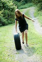 Young woman pushing tire