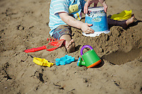 A small child having some grown up assistance making sand castles on Coral Bay Beach, Cyprus