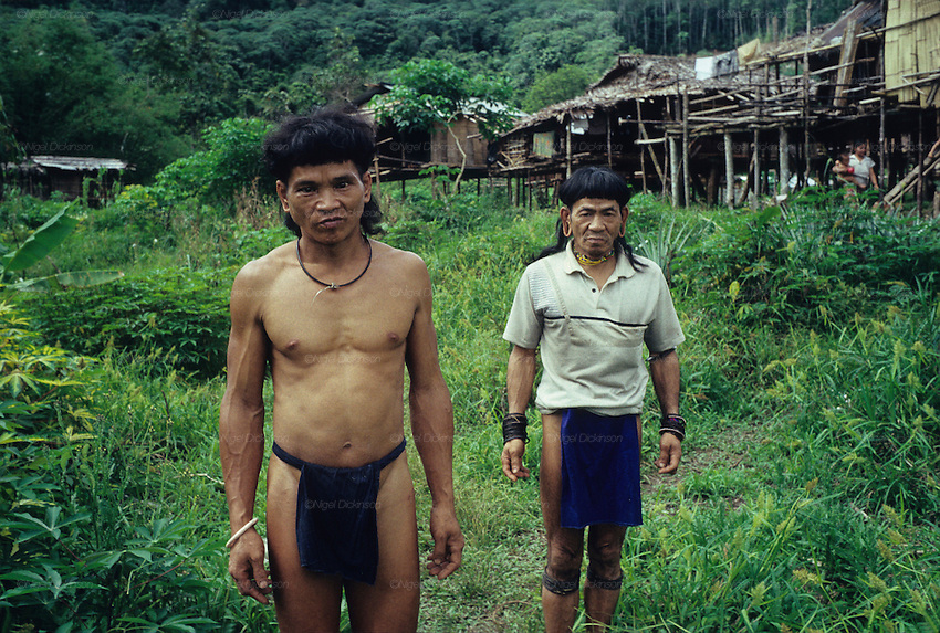 Twenty three years ago: Baru and Banai Tebai standing in front of a temporary 'sulap' structure, made from a mixture of timber, bamboo and rattan. Semi-nomadic Penan, indigenous hunter-gatherers, dressed in traditional 'chawats' loincloth. Long Tegang, Limbang district, Sarawak, Borneo 1989<br /> <br /> Semi-Nomadic Penan, MALAYSIA. Sarawak, Borneo, South East Asia.&nbsp;Penan men with their sulap settlement  . Tropical rainforest and one of the world's richest, oldest eco-systems, flora and fauna, under threat from development, logging and deforestation. Home to indigenous Dayak native tribal peoples, farming by slash and burn cultivation, fishing and hunting wild boar. Home to the Penan, traditional nomadic hunter-gatherers, of whom only one thousand survive, eating roots, and hunting wild animals with blowpipes. Animists, Christians, they still practice traditional medicine from herbs and plants. Native people have mounted protests and blockades against logging concessions, many have been arrested and imprisoned.