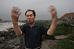"""A salt-field worker expresses his complaints with great anger in Lianyungang City: """"I can't bear any longer the pungent smell of the gas from the chemical factories when the wind blows."""" Jiangsu Province. July 19, 2008."""