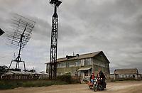 Remote streets of Khailino with Soviet housing and radio antennas.
