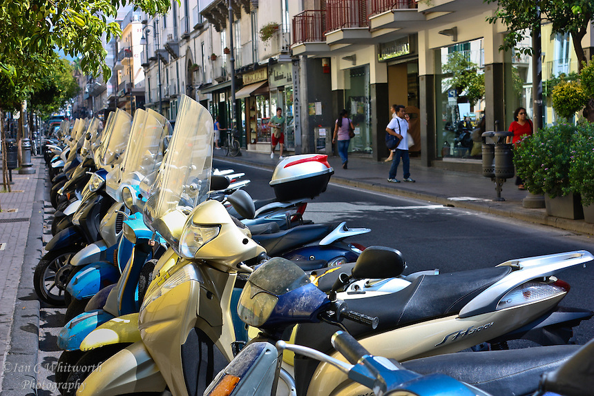Scooters & motor bikes parked on a street in Italy.