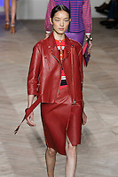 Fei Fei Sun walks the runway in a leather motorcycle jacket, pink/navy/white one-piece bathing suit, and red leather wrap skirt, by Tommy Hilfiger for the Tommy Hilfiger Spring 2012 Pop Prep Collection, during Mercedes-Benz Fashion Week Spring 2012.