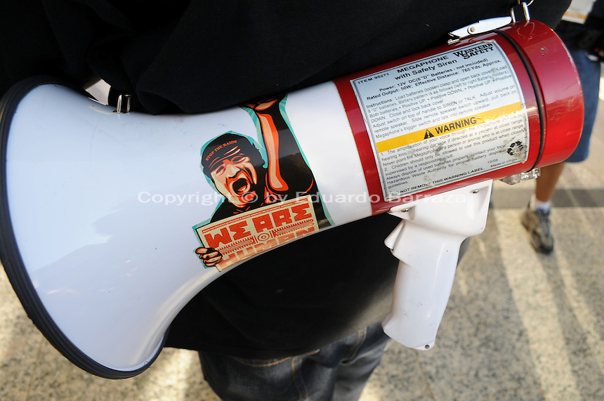 Phoenix, Arizona. September 17, 2012 - A small crowd of demonstrators in Phoenix, Arizona gathered to mark one year since the beginning of the Occupy Movement that opposes Wall Street and large corporations that represent the one percent who control wealth in the United States. In this photograph, a megaphone used by organizer Orlando Arenas hangs in his back as he leads participants of the Occupy Phoenix group to chant in protest against the Wells Fargo Bank. Photo by Eduardo Barraza © 2012