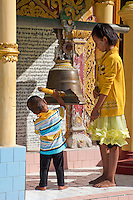 Myanmar, Burma.   Umin Thounzeh, Buddhist Shrine on Sagaing Hill, near Mandalay.  A big sister teaches her brother to strike the temple bell, to drive evil spirits from the temple and to announce the arrival of the devotee.