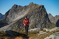 Female hiker in rugged mountain landscape with Kråkhammartind in the background, Moskenesøy, Lofoten Islands, Norway