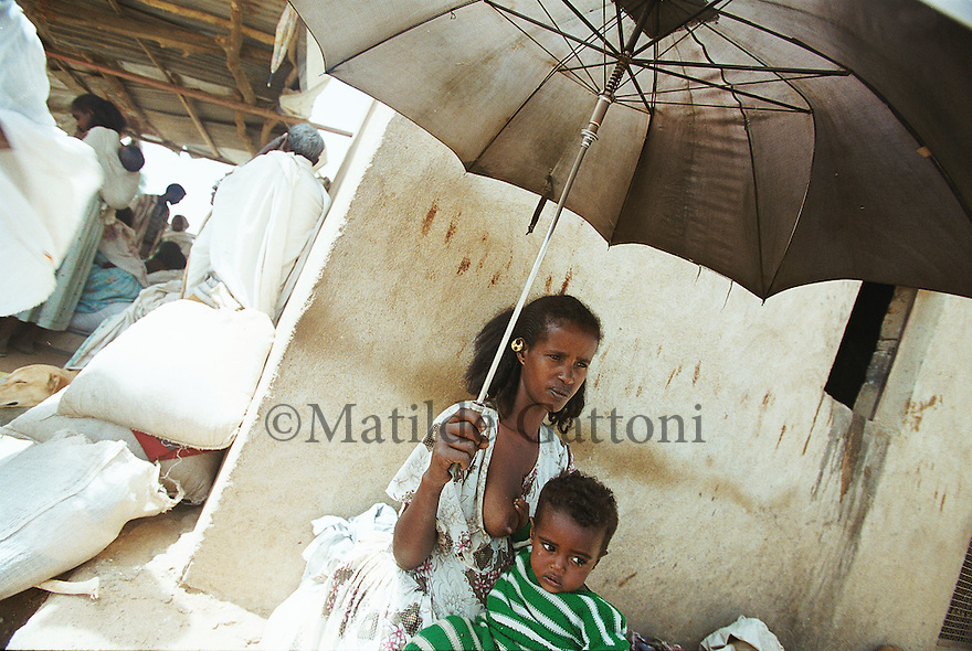 Eritrea - Debub- Mother queing for food distribution. As a result of 30 years of war for independence against Ethiopia (from 1961 to 1991) and another 3 years from 1997 to 2000, there are 50,000 Eritreans currently living in internally displaced (IDP) camps throughout the country. These IDPs have fled three times in the last 10 years, each time because of renewed military conflict. They lived in relatives' homes when lucky enough, but mostly, the fled to the mountains, where they attempted to do what Eritreans do best, survive. Currently there is no Ethiopian occupation in Eritrea, but landmines prevent the IDPs from finally going home. .It is estimated that every Eritrean family lost two or three members to the war which makes the reality of the current emergency situation even more painful for Eritreans worldwide. Currently, the male population has been decreased dramatically, affecting the most fundamental socio-economic systems in the country. Among the refugee population, an overwhelming majority of families are female-headed, severely affecting agricultural production. For, IDPs in particular, 80% of households are female-headed..The unresolved border dispute with Ethiopia remains the most important drawback to Eritrea's socio-economic development, as national resources (human and material) continue to be prioritized for national defense. Eritrea is vulnerable to recurrent droughts and variable weather conditions with potentially negative effects on the 80 percent of the population that depend on agriculture and pastoralism as main sources of livelihood. The situation has been exacerbated by the unresolved border dispute, resulting in economic stagnation, lack of food security and increased susceptibility of the population to various ailments including communicable diseases and malnutrition..
