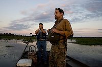 Guide Ron Russell, Gator Getter Consutants, calls out to surrounding alligators using a sound mimicking a female as hunter Jeff Bannister, of Greenville, watches during their alligator hunt along the Cooper River Oct. 5, 2008 in Moncks Corner, South Carolina. After 40 years, the Department of Natural Resources (DNR) issued 1,000 permits to hunt alligators in South Carolina in an effort to control the population which numbers more than 100,000. (Paul Zoeller/pressphotointl.com)