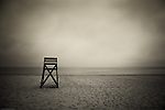 Lifeguard stand on deserted beach with distand seagulls