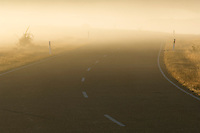 Poor visibility on fog covered road at sunrise